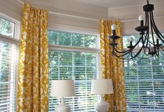 How to hang curtains on an angled or bay window:  http://emilyaclark.blogspot.com/2012/09/hanging-curtains-on-angled-windows.html