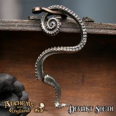 Alchemy Gothic E309 Kraken Stud Ear-Wrap (left)  Faux-stretch piercing pewter octopus tentacle ear-wrap with surgical steel ear-post.