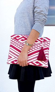 Red tribal-inspired woven clutch with a yarn tassel along the top zipper closure.