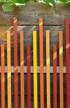 Liven up a dull wooden fence with this colorful piece of art made from painted square dowels.