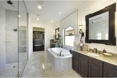 Floor to ceiling glass envelops a luxurious walk-in shower. The TwinEagles new home community in Naples, Florida is coming soon from Minto Communities.