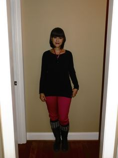 Black sweater, pink skinny pants, houndstooth legwarmers, black boots, black heart necklace with pink velvet ribbon