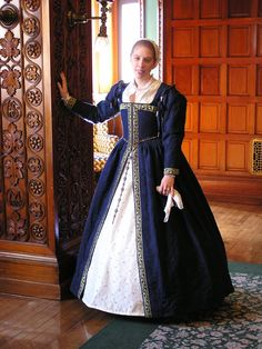 Basic Elizabethan-blue kirtle, a partlet, chemise, hoopskirt and decorated with trim.