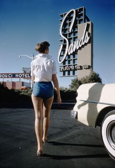 Vintage Las Vegas Photo, 1955. A model poses next to a '54 Buick Century outside the Sands Hotel with Sans Souci Hotel seen across the Las Vegas Strip. Photos by Hy Peskin.