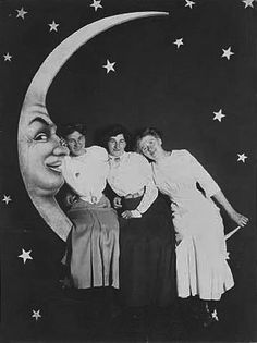 girls leaning into the paper moon