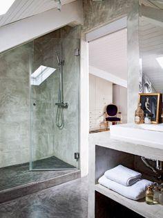 Baño con ducha abuhardilla revestida en microcemento
