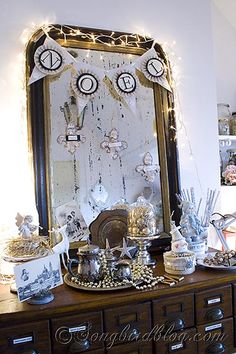 A vintage inspired Christmas decorative display in front of a vintage French mirror. See more details at http://www.songbirdblog.com