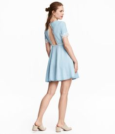 Light denim blue. Short dress with inset lace details and a cut-out section at back. Short sleeves, buttons at back of neck, and seam at waist. Flared,