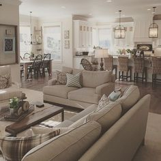 Neutral coloured room with beige couch and love seat with hardwood steel-legged table and open concept kitchen living room