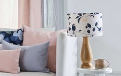 Wren & Cherry lampshade made in the UK by designer Lorna Syson. This floral lampshade is inspired by garden flowers and birds. One of our best-loved British birds, here the tiny wren creates a delicate silhouette against the slim branches of the cherry tree.