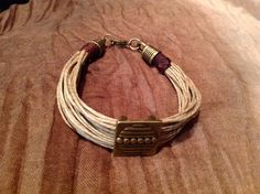 Pulsera de múltiples hilos de cáñamo con pieza decorativa en bronce. Multiple hemp cords bracelet with bronze piece.