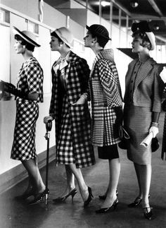 Four models wearing dress suits at a race track betting window, at Roosevelt Raceway, USA, 1958.