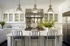 My stools with stainless steel appliances and white cabinets.