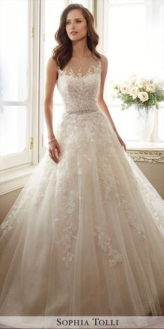 Sleeveless misty tulle and sequin full A-line gown features an illusion bateau neckline trimmed with hand-beading, lace appliqué sweetheart bodice over sequin tulle, crystal encrusted beaded waistline, appliqués trail down skirt, back corset, chapel length train.