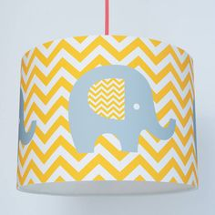This handmade paper lampshade features a retro elephant on a chevron backdrop.The lampshade would look great in a contemporary nursery but its bold graphic style means it would work equally well in older children's rooms. The shade is made to a professional standard by hand from high quality art paper attached to a PVC fire-resistant backing. It can be made as a ceiling pendant or as a shade for a lamp.Art paper on a PVC backing.Shade is 30cm in diameter and 22cm in height.