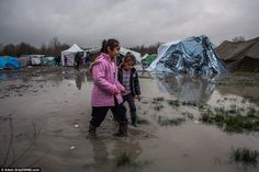 Misery: Sisters Havin, six, and Hana Ttahsin, four, from Kurdistan walk through awful muddy conditions at the Grand-Synthe migrant camp which holds about 3,000 migrants in Dunkirk, France