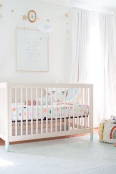 Pastel Nursery with Star Accents - the natural wood crib and fun pops of color are so on-trend! (via @laybabylay)