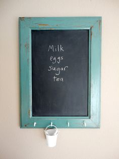 This classic chalkboard is made from a salvaged cabinet door with a worn paint finish. The warm oak wood tones show through the distressed edges of the turquoise paint. A miniature white metal pail keeps your chalk handy and hangs from the row of added white key hooks.      Frame measures 20 inches tall by 14.75 inches wide.    Chalkboard panel measures 15.5 inches tall by 10.25 inches wide.    Includes pail and a small packet of chalk tied in ribbon.  It is ready to hang with 2 d-rings on…