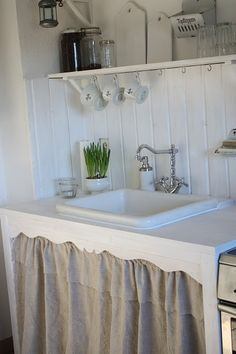 cute kitchen in white.love the sink skirt trim Grey Cabinets, Sink Shelf, Farmhouse Sink Kitchen, Curtains, Vintage Kitchen, Pantry Laundry Room, Sink Skirt, Shabby Chic Kitchen, Cottage Kitchens