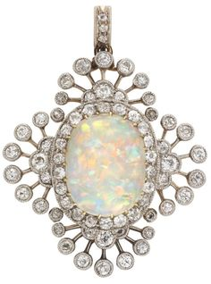 An Edwardian opal and diamond brooch.           An Edwardian opal and diamond brooch, the oval cabochon-cut opal measuring approximately 14.3 x 11mm, yellow gold claw-set to the centre of an old-cut diamond cluster surround, all within a border of old-cut diamond sprays forming a quatrefoil design, all diamonds millegrain-set in silver to a yellow gold mount, with detachable brooch fitting and diamond-set pendant loop, gross weight 8.7 grams, circa 1900. Via Bentley & Skinner.