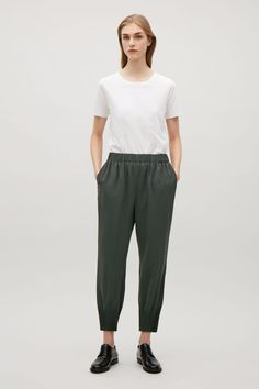 With pleated hems creating a tapered leg, these trousers have has a slight dropped crotch and an elastic waistband. Designed to sit just above the hips, they're completed with has subtle in-seam pockets and raw-cut finishes.
