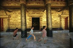 "Children run past the gilded walls of Wat Mai, or the New Temple, in the ancient city of Luang Prabang, Laos. Known as the ""City of the Golden Buddha,"" Luang Prabang has an array of historic Buddhist temples. Luang Prabang, Laos, Golden Wall, Golden Buddha, Buddhist Temple, How To Make Light, Color Of Life, National Geographic, Beautiful Places"