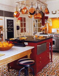 Warmth is the focus of this Hollywood kitchen designed by Peter Durham. Every detail — from block-printed Indian fabric lining cabinet doors to a brick-lined wood-burning fireplace — radiates cozy charm. The hand-stamped floor tiles are by Carocim from Studio 11. The countertops and mantel stone are from Solistone. The Rohl sinks have fittings from Ann Sacks.   - HouseBeautiful.com