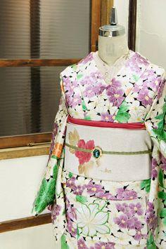 黒地に白と紫が優美な夕化粧のような花と、緑と白凛と美しい山百合のような花模様が一面に染め出された綸子袷着物です。