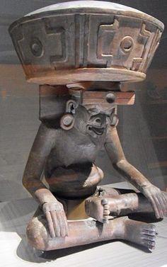 Cette représentation du dieu du Feu est modelée dans le style de la côte du Golfe. Huehueéotl se distingue ici par le grand encensoir qu'il porte sur la tête et où figure le symbole du quinconce.Xiuhtechtli