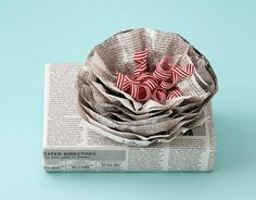 """""""You may have seen newspaper repurposed as wrapping before, but Murnane's blossoming topper — which sprouts striped ribbons — keeps this classic current.""""    Read more: Creative Gift Wrap Ideas - Designer Gift Wrap - Country Living"""