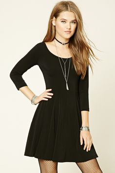 A knit dress featuring a skater silhouette, strappy back, a round neckline, and 3/4 sleeves.
