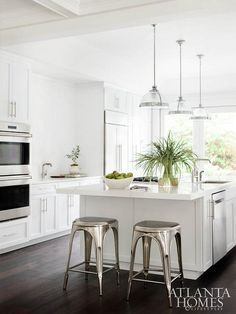 White kitchen features three Restoration Hardware Classic Clemson Pendants illuminating a white center island fitted with a stainless steel sink next to a stainless steel mini beverage fridge lined with industrial backless counter stools, Remy Backless Stools.