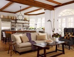 """Designers Barbara Westbrook and Kim Winkler opened the kitchen of an Atlanta house to the family room. """"The space had to accommodate a family of five, as well as a lovable golden retriever,"""" says Westbrook. """"The openness makes it easy for everyone to mingle and not feel separated. But it was important that the two rooms look coordinated."""" They chose a neutral and white palette, with a mix of rustic antiques and unfussy contemporary pieces. Stainless steel Sub-Zero."""