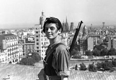 Marina Ginestà, pictured here at age 17, worked as a journalist during the Spanish Civil War and was a member of the Socialist Youth. Standing on top of the Hotel Colón in Barcelona, it was one of the only times she was armed.