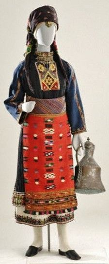 Festive costume from Kavakli (eastern Roumelia). Early 20th c. With some variations, this costume was worn by married as well as single women in the 11 Greek villages of the Kavakli district (now part of Bulgaria). After the population exchange of 1922-23, its inhabitants settled in Thessaly, Macedonia & Thrace. The main item of the costume is the tsoukna, a sleeveless one-piece dress with an embroidered hem; its type of embroidery, patterns & colors denoted the social situation of the…