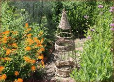 How to Make a Wicker-style Garden Obelisk From a Tomato Cage DIY Dieses Handwerk ist voller Charme, Tomato Cage Diy, Tomato Cage Crafts, Tomato Cages, Fall Topiaries, Topiary, Obelisk, Modern Plant Stand, Paper Rosettes, Plant Supports