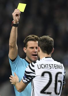 Juventus' Swiss defender Stephan Lichtsteiner is handed a yellow card  during the UEFA Champions League round of 16 second leg football match FC Porto vs Juventus at the Dragao stadium in Porto on February 22, 2017. / AFP / FRANCISCO LEONG