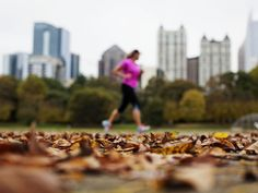 Leaves lay on the ground as a woman jogs past the midtown skyline in Piedmont Park in Atlanta.   David Goldman, AP