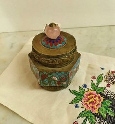 Where can you buy an ANTIQUE POPPY FLOWER CLOISONNE TOBACCO OPIUM JaR HUMIDOR? Here and it has 6 fabulous panels of cloisonne with a lattice pattern and trailing poppy flowers. The brass band along the top and the bottom have flowers, the longevity knot and fish. It sits on three brass feet and has a lovely knob of rose quartz on the lid. It has the original patina and is in great condition.  https://www.etsy.com/listing/193377714 $55.95