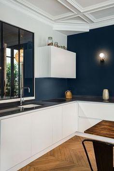 Rénovation appartement Haussmanien avec création de la cuisine dans la pièce principale. Jeux de contraste entre le blanc des façades et le foncé des murs.