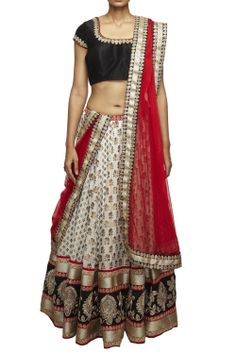 Off-white brocade lehenga with gold motifs and a hand-embroidered border, black raw silk blouse and red net dupatta, by Neha Gursahani. Product measurement : Blouse M size: 36 chest #studiorudraksh.com #neha gursahani