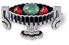Fruit bowl brooch CARTIER PARIS, 1925 Platinum, yellow gold, pear-, lozenge-shaped and square single- and baguette-cut diamonds, one emerald cabochon and two ruby cabochons, onyx, black enamel.   Sold to Mrs William K. Vanderbilt.  5.21 x 3.40 x 1.0 cm