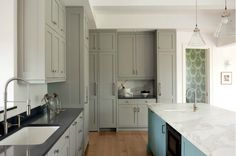 Two-tone kitchen with gray shaker kitchen cabinets with polished black granite