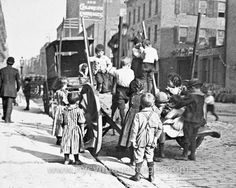 A street scene of children playing on a cart, during America's Gilded Age in NYC, c.1890. Location: Cherry Street and Rutgers Slip, on the Lower East Side, of Manhattan. ~ {cwlyons} ~ (Image: NYC Vintage)
