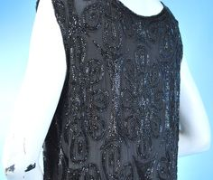 """1920s Dazzling Beaded Sheath Dress Labelled """"Dresser, Paris"""". Beautiful interlocking design elements in an overall pattern done with seed beads and bugle beads. All in black on a black silk crepe. Detail"""