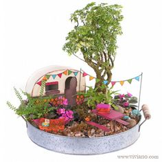 """Happy Camper Fairy Garden ~ Everyone needs a weekend getaway, including fairies. This campsite lets them (and you) unwind and enjoy the great outdoors, glamping-style! Rustic round metal tray planted with African violets, ferns, and a bonsai tree features colorful miniature accessories, including a trailer, hammock, flag banner, and picnic table and basket. Created by Viviano Flower Shop with tiny items from the """"Gypsy Garden"""" collection by Studio M and artist Genevieve Gail."""