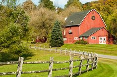Classic red barn in Kent Connecticut showing curved split-rail fence and fall colors starting to turn