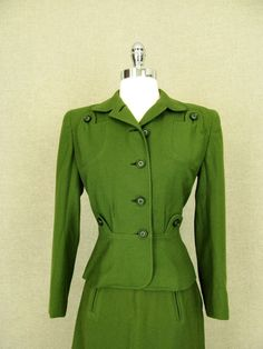 """1940s Military Style Wool Skirt Suit * Beautiful green wool suit with military style * Fitted jacket with stylish button-up pockets at top * Satin lining; weights sewn into the bottom of jacket * Skirt has slight a-line and faux slit pockets * Label: None MEASUREMENTS: (laid flat; double measurements for estimated circumference) JACKET Bust: 18"""" Waist: 14.5"""" Bottom hem: 17.5"""" Shoulder to Hem: 20.5"""" CONDITION: Excellent SKIRT Waist: 13.5"""" Hip: 19"""" A-line: 24"""" Waist to hem..."""