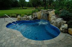 Spool ( cross between a spa and a pool) with moss rock waterfall. Great idea for small backyards. www.longislandhottub.com