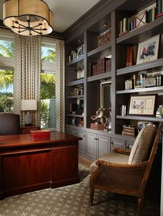 With a glossy mahogany desk and expansive gray built-ins, this home office exudes classic sophistication. A neutral color scheme keeps the space grounded.